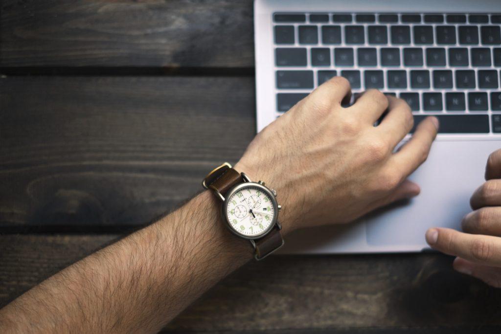Homme sur un ordinateur regardant sa montre